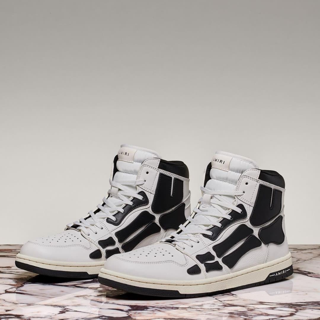 GRUNGE AESTHETIC: embossed skeleton design defines these Skel-Top sneakers from @amiri. Crafted from leather in a black and white colorway, the sneaker is recognized by its athletic silhouette and retro styling.  Available on genteroma.com and in store at Via del Babuino, 185.  #GenteRoma #Amiri #FW21