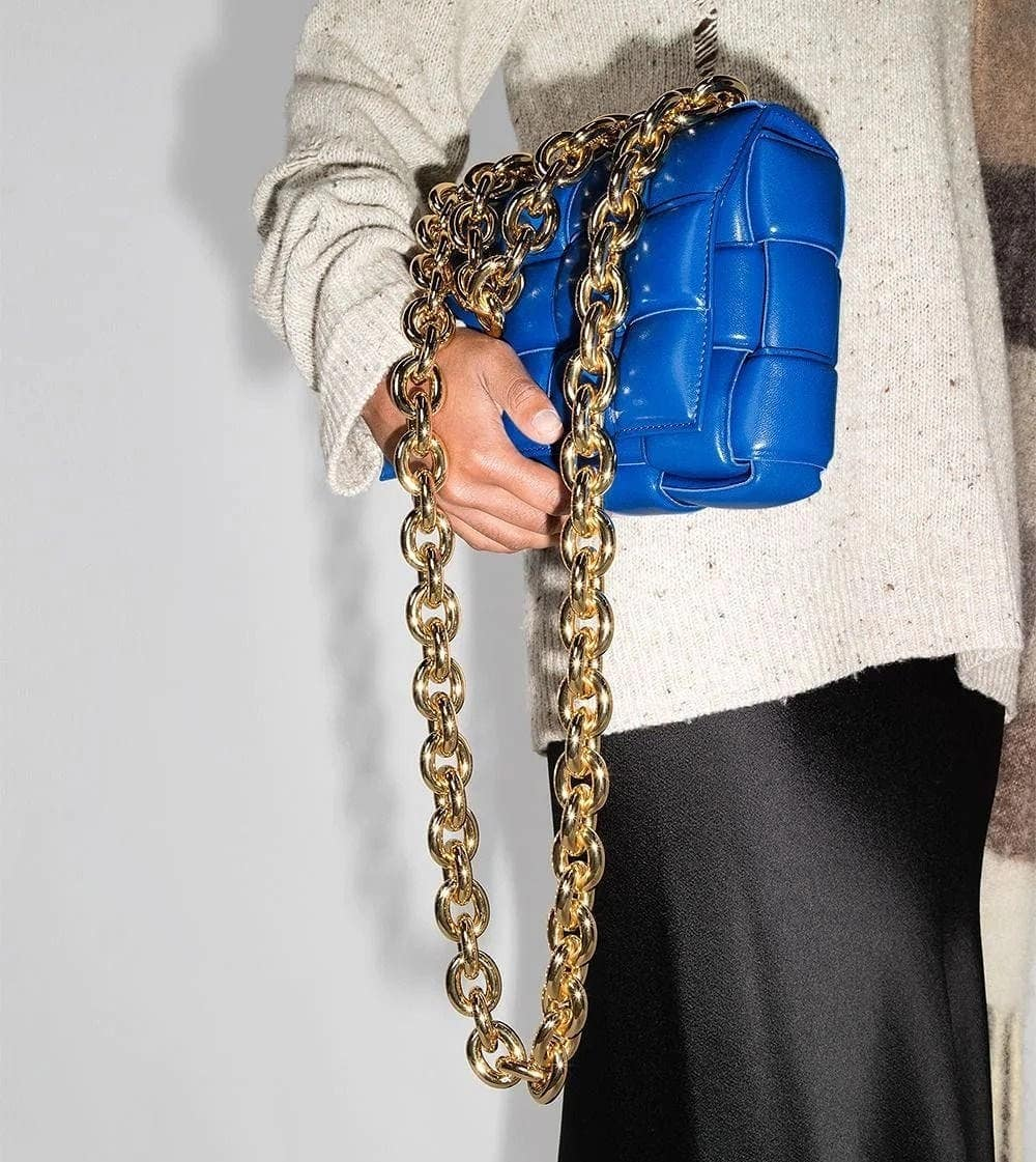 COBALT BLUE: one of Bottega Veneta's most coveted bags is the Padded Chain Cassette, presented this season in a deep blue with a chunky gold chain. Elevate your look with this statement piece.  Available ongenteroma.comand in store at Via del Babuino, 77.  #GenteRoma #BottegaVeneta #FW21