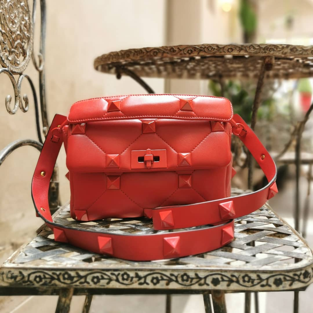 ROUGE PUR: Valentino Garavani's accessories are instantly recognizable. This 'Roman Stud' tote has been made in Italy from quilted red leather embellished with exaggerated pyramid hardware.  Available on genteroma.com and in our boutiques.  #GenteRoma #ValentinoGaravani #FW21